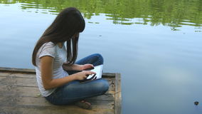 Girl using tablet pc and relaxes by the lake sitting on the edge of a wooden jetty near the water surface stock video
