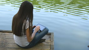 Girl using tablet pc and relaxes by the lake sitting on the edge of a wooden jetty near the water surface.  stock footage