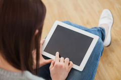 Girl using a tablet pc sitting on the floor Stock Images