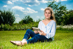 Girl using tablet pc and sitting on the green grass. Beautiful young girl using tablet pc and sitting on the green grass Royalty Free Stock Photography