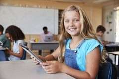 Girl using tablet in school class smiling to camera close up stock image