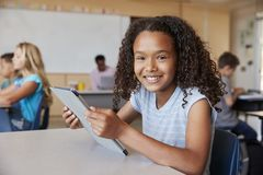 Girl using tablet in school class smiling to camera close up royalty free stock image