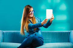 Girl using tablet taking picture of herself blue color Royalty Free Stock Image