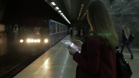 Girl using a tablet and waiting for train at subway station. brunette girl stays in subway and using touchpad. Fashionable gadget. The concept is always in stock video