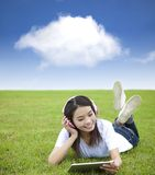 Girl using touch pad computer with headphone Royalty Free Stock Images