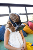 Girl using virtual reality headset while sitting in library Royalty Free Stock Photos