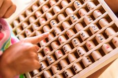 Girl using a wooden board with mathematical multiplication operations, a game to learn