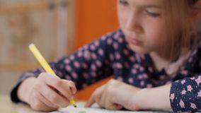 Girl using yellow felt-tip pen draws on paper. Little girl drawing - closeup shot stock footage