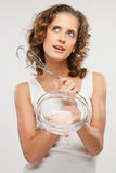 The girl with utensils. A smiling girl hold a glass bowl and a nimbus Stock Photo
