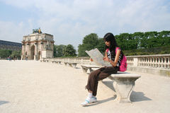 Girl on Vacation. Paris. Girl looking at map. Arc de Triomphe du Caroussel in the background stock photos