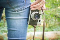 Girl on vacation in the forest. With a vintage retro camera royalty free stock images