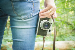 Girl on vacation in the forest. With a vintage retro camera royalty free stock photography