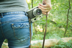 Girl on vacation in the forest. With a vintage retro camera royalty free stock image