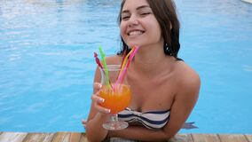 Girl on vacation by the pool happy young woman in bikini drinks vivid cocktail in blue water of pool. Girl on vacation by pool happy young woman in bikini drinks stock video footage