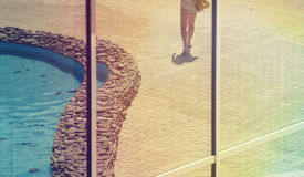 Girl is on vacation. Reflected girls feet in the window of the resort hotel Royalty Free Stock Photos