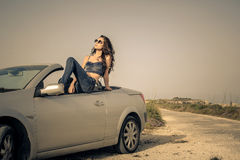 Girl on vacation. Relaxing while sitting in her car Royalty Free Stock Photography