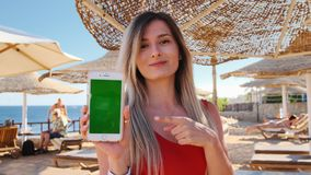 Girl on vacation show the green screen smartphone outdoor. Close up woman hand holding and using mobile smart phone with
