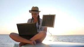 Girl in vacation sits on roof car with solar array charges laptop in backlight, female sitting on vintage car with. Computer powered by battery, background blue stock video footage
