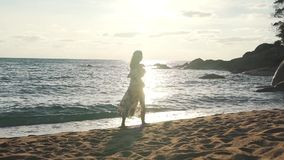 Girl on vacation walking by the ocean with backpack stock footage