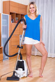 Girl vacuuming floor and furniture Royalty Free Stock Photos