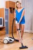 Girl vacuuming floor Royalty Free Stock Photo