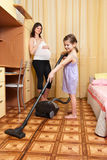 The girl vacuums a floor Stock Photo