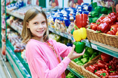 Girl with varicolored bell peppers in supermarket Stock Photo