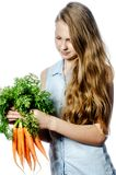 The girl with vegetables. The long-haired young girl with carrots Royalty Free Stock Image