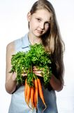 The girl with vegetables. The long-haired young girl with carrots royalty free stock photography