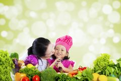 Girl with vegetables kissed by mother. Cute little girl wearing a cooking hat with vegetables on the table and kissed by her mother, shot with bokeh background stock images