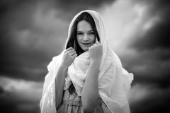 Girl with veil. In front of clouds Stock Images