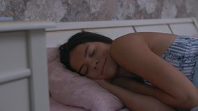 Girl wakes up in bed. The girl is very cute sleeping with a smile on her lips stock footage