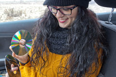 Girl very happy in a car with two cds. In her hands Stock Photos