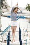 The girl in the vest and shorts on the deck Stock Photos