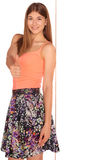 Girl in a vest and skirt behind white wall Stock Photography
