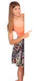 Girl in a vest and skirt behind white wall Royalty Free Stock Photography