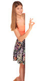 Girl in a vest and skirt behind white wall Royalty Free Stock Images