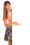 Girl in a vest and skirt behind white wall Stock Image
