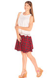 Girl in a vest and skirt behind white wall. Pretty girl in a vest and skirt behind white wall Stock Photography