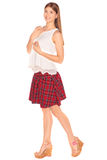 Girl in a vest and skirt behind white wall Stock Images