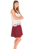 Girl in a vest and skirt behind white wall Royalty Free Stock Photo