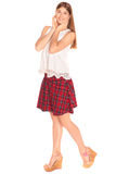 Girl in a vest and skirt behind white wall Stock Photos
