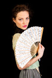 Girl in Victorian dress with fan in her hand. Girl in Victorian dress with a fan in her hand looking in the camera on a black background royalty free stock images