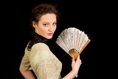 Girl in Victorian dress with fan in profile. Girl in Victorian dress with a fan in her hands seen in profile on a black background Stock Image