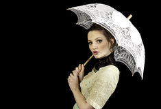 Girl in Victorian dress holding a lace umbrella. On a black background Royalty Free Stock Images