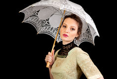 Girl in Victorian dress holding a white umbrella. And looking in the lens of the camera on a black background Royalty Free Stock Photos