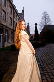 Girl in Victorian dress in a old city square in the evening stock images