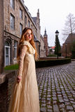 Girl in Victorian dress in a old city square. Model in a white Victorian dress in the historic city of Leuven with medieval church and antique houses Royalty Free Stock Photography