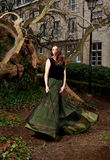 Girl in Victorian dress in the park. In front of a house and trunks of trees Royalty Free Stock Photo