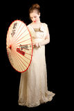 Girl in Victorian dress playing with Chinese umbrella Royalty Free Stock Photography